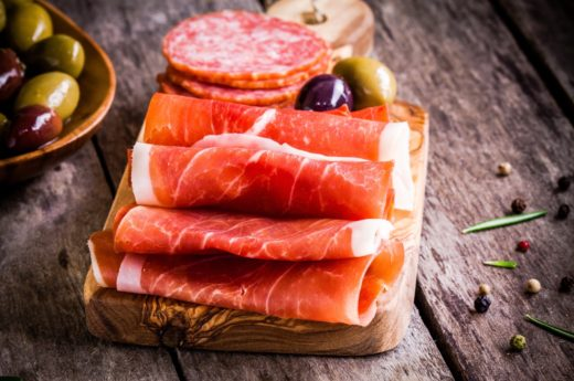slices of prosciutto with olives and salami on cutting board