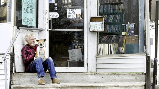 "Walter Lance and his 8-year-old dog, Shep, take a break Thursday outside Artios Books, the Auburn bookstore where Lance works. Shep serves as the shop's doorbell, letting Lance know when customers enter. A bowl of dog treats kept on the counter ""turns the doorbell off."" Lance said the store mostly stocks used books, with romance novels and Westerns being hot on the used-book scene. ""And of course, Stephen King,"" he said. (Daryn Slover/Sun Journal)"